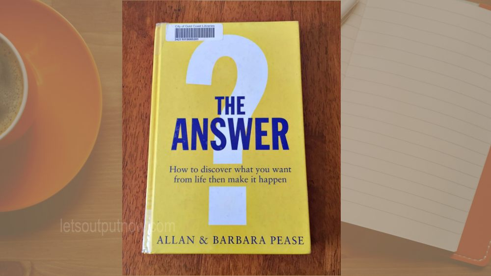 The Answer Allan & Barbara Pease How to discover what you want from life then make it happen 黄色い表紙の洋書 バックグランドにはノートとコーヒー